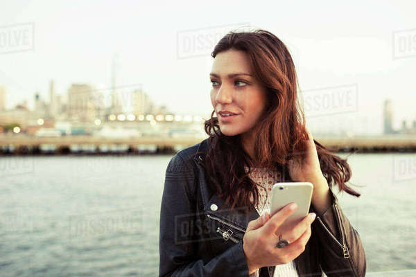 Thoughtful woman holding smart phone with One World Trade Center in background Royalty-free stock photo