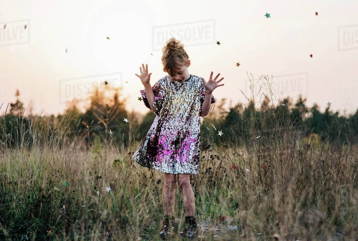 Girl dancing in a sparkly dress at sunset with star confetti falling Royalty-free stock photo