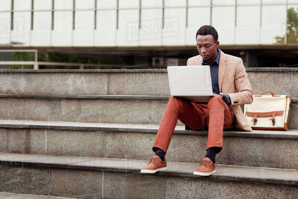Businessman using laptop while sitting on steps Royalty-free stock photo