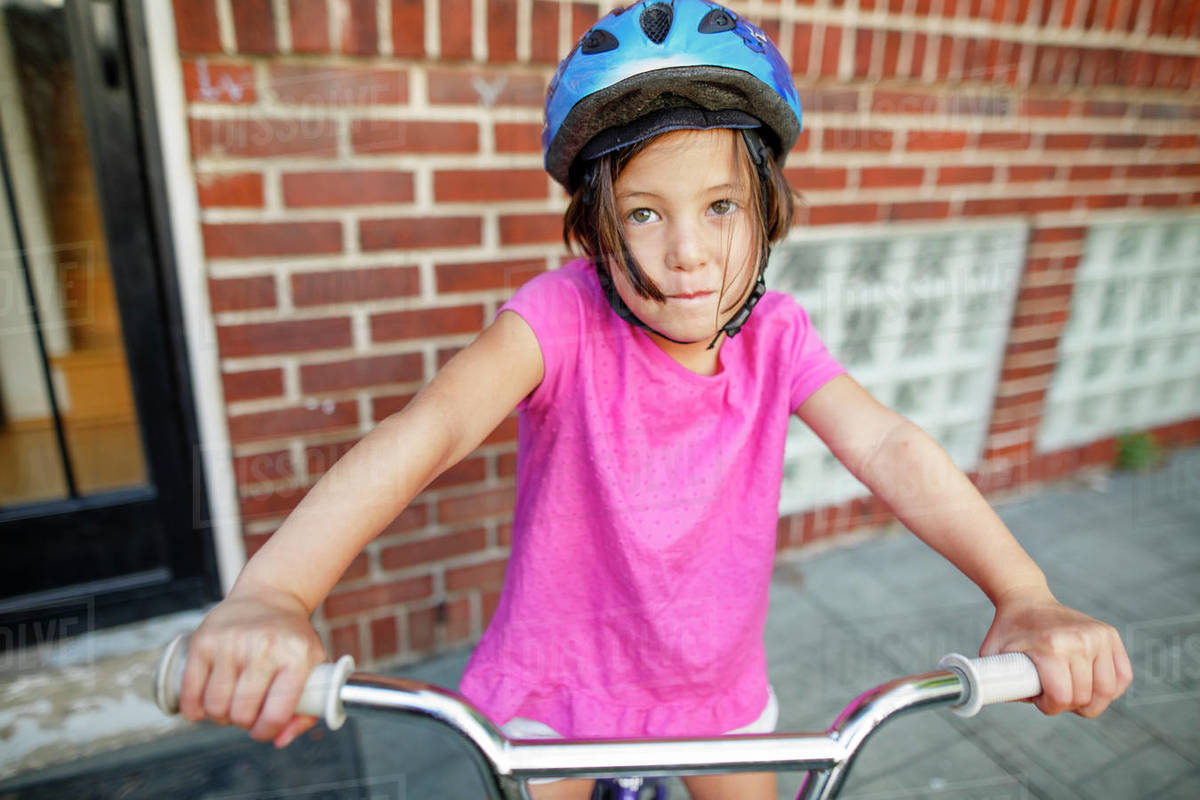 A cute little girl sits on her bike in front of house wearing a helmet Royalty-free stock photo