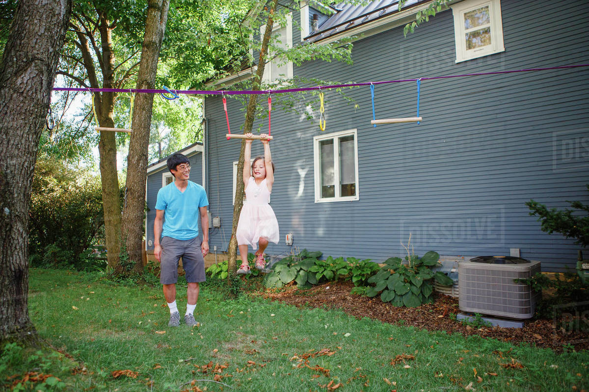 A cute girl hangs from a bar while her proud smiling father watches Royalty-free stock photo