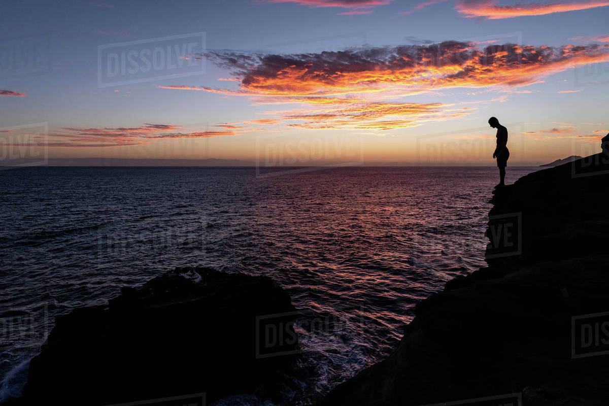 Cliff diver prepares to jump into the ocean at sunset in hawaii Royalty-free stock photo