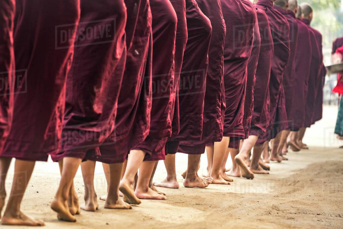 Detail shot of feet of monks waiting in queue while receiving alms, Nyaung U, Myanmar Royalty-free stock photo