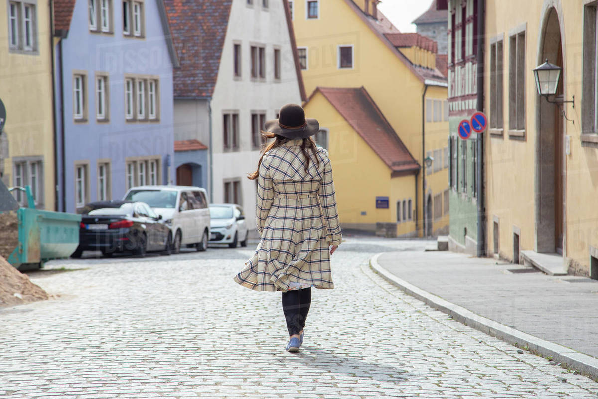 A woman wearing a long coat walking the streets of a medieval town. Royalty-free stock photo