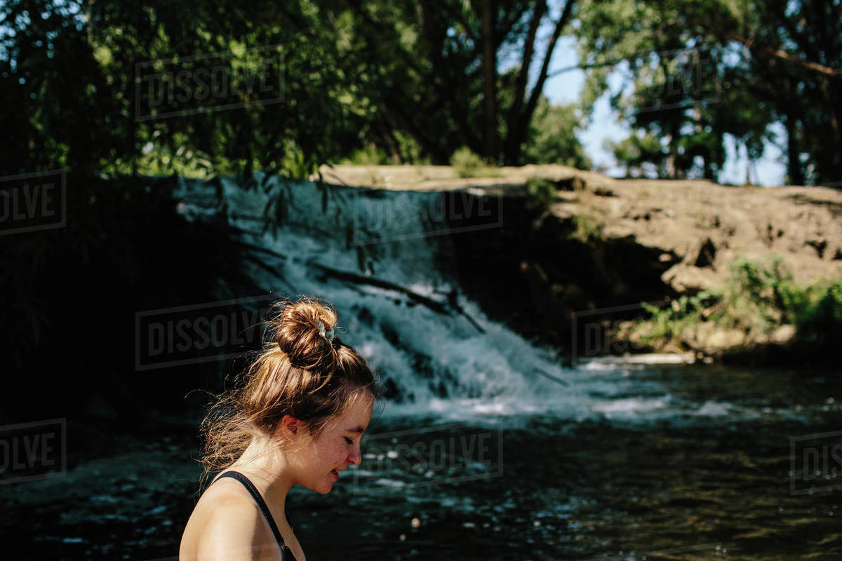 Close up of teen girl walking standing near a small waterfall Royalty-free stock photo
