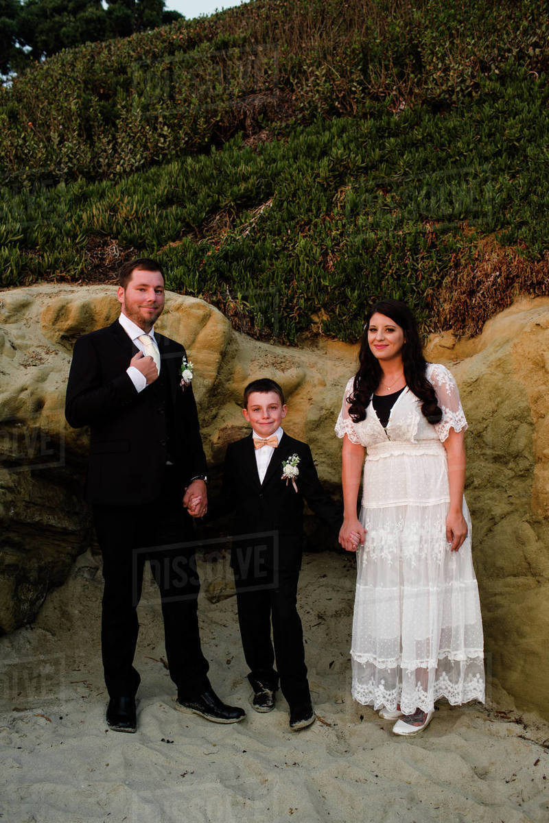 Newlyweds & Son Posing Next to Rocks on Beach at Sunset in San Diego Royalty-free stock photo