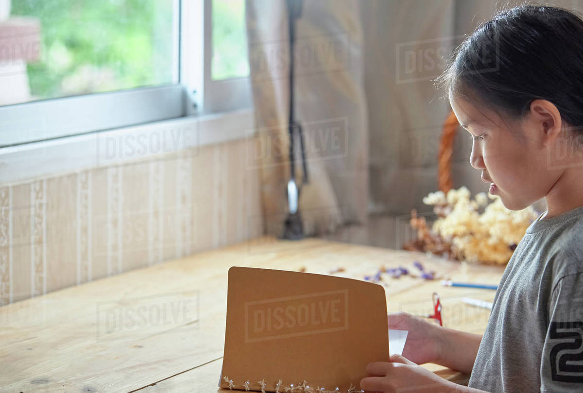 A girl reading a book on the big wooden table Royalty-free stock photo