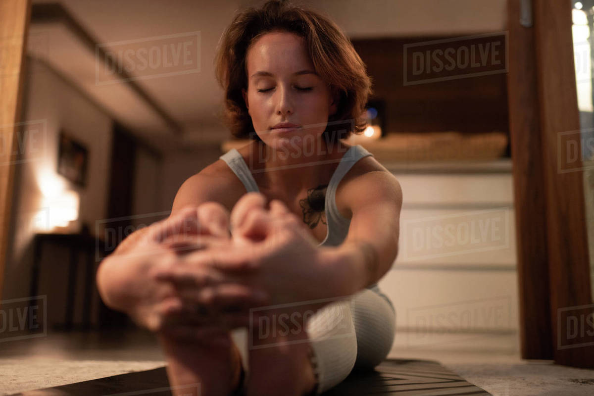 Relaxed woman doing Seated Forward Bend Royalty-free stock photo