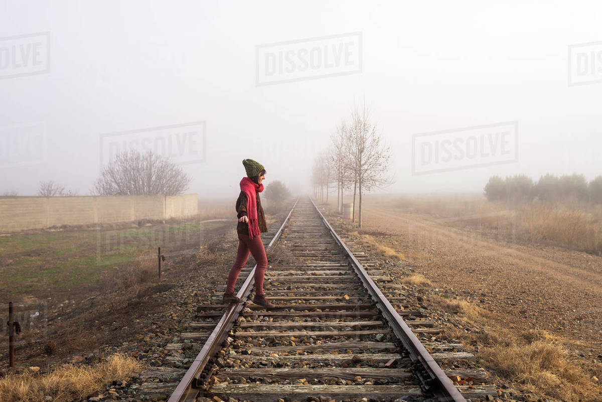 Side view of a girl balancing on train rail while walking Royalty-free stock photo