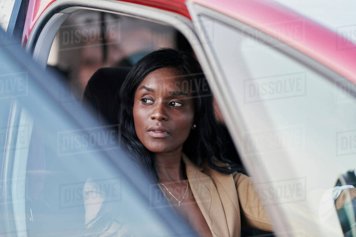Portrait of a black woman in a brown suit with the door open to Royalty-free stock photo
