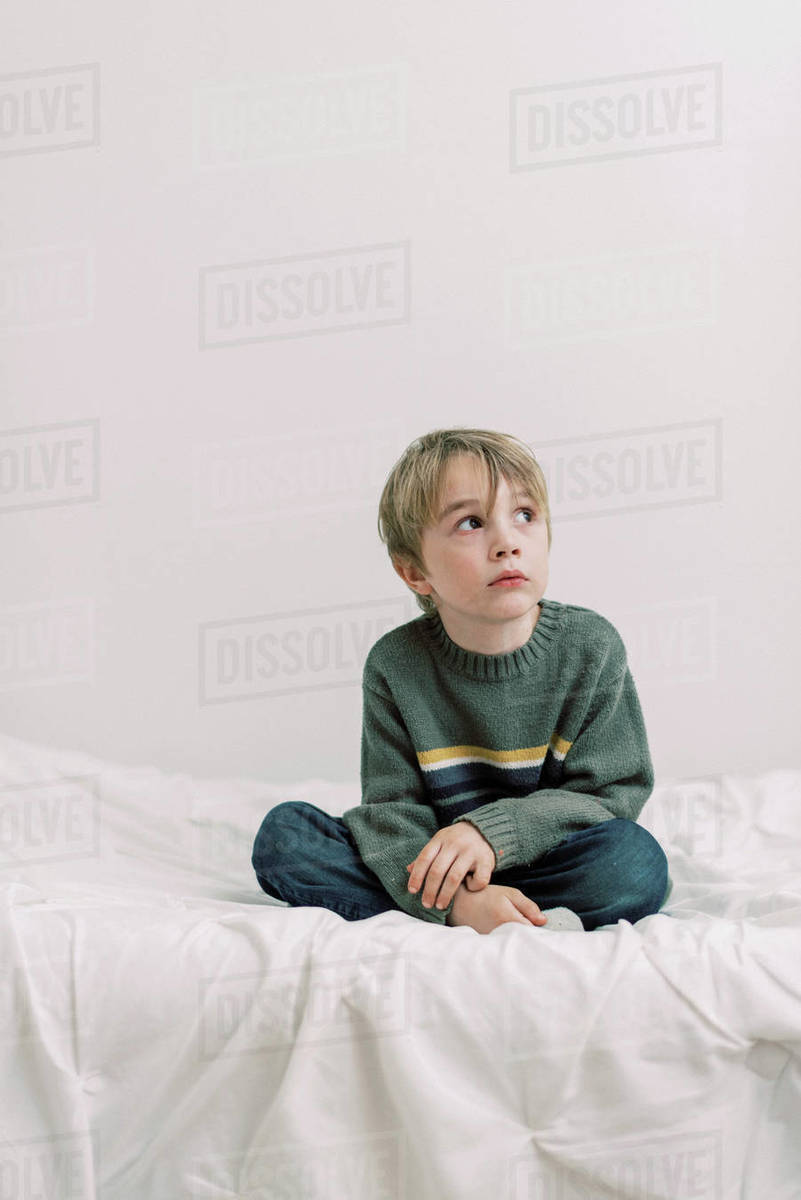 Little bored boy sitting on a bed Royalty-free stock photo