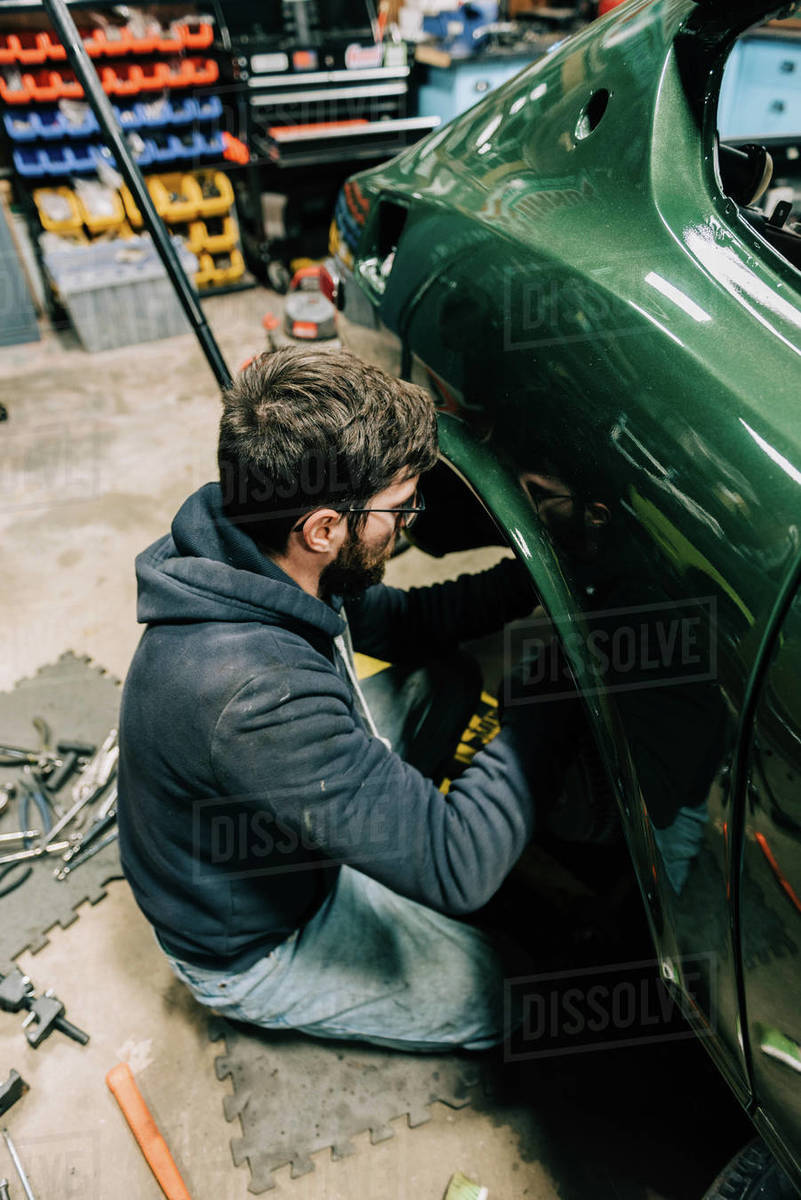 Photo of a young man in a garage performing repairs on old car Royalty-free stock photo