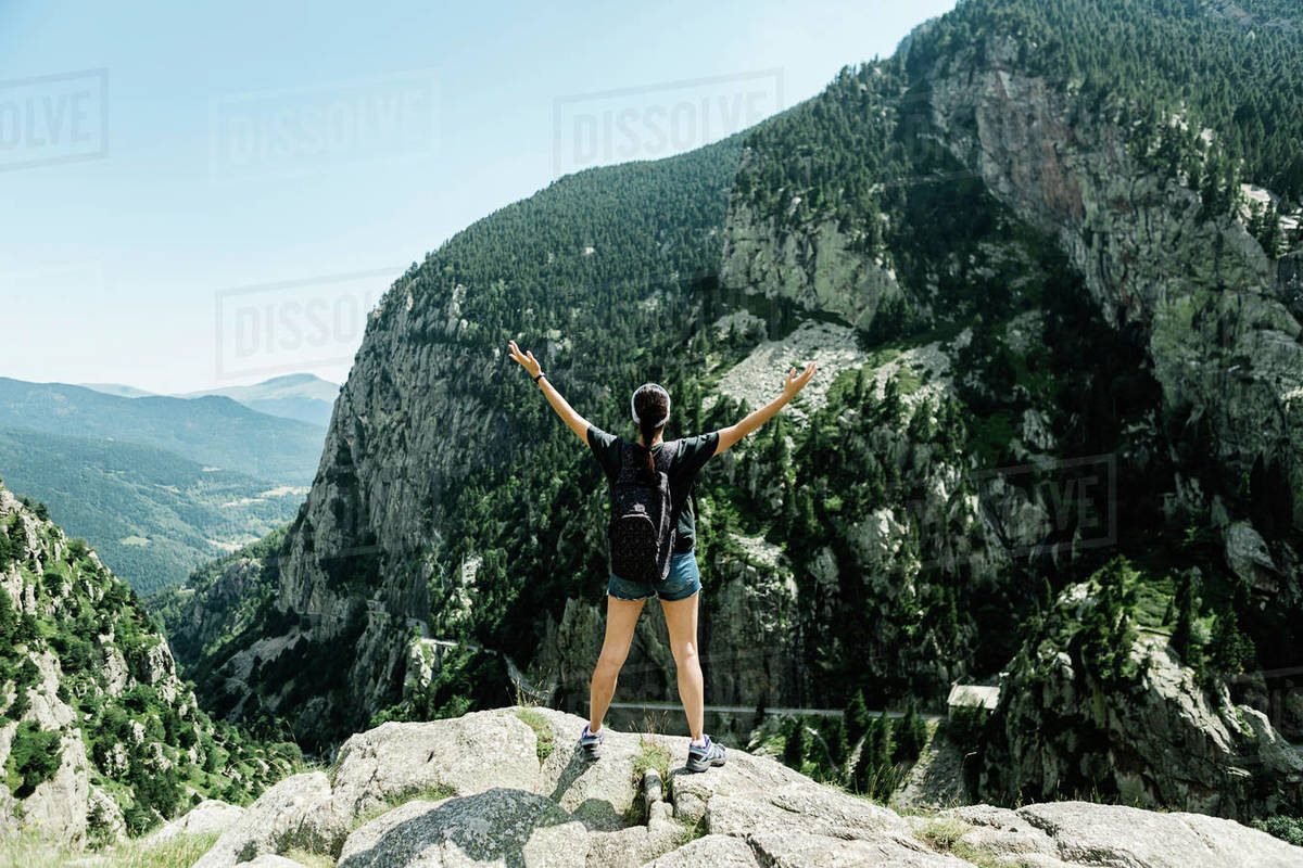 Rear view of an adventure woman raising her hands on the top of a mountain Royalty-free stock photo