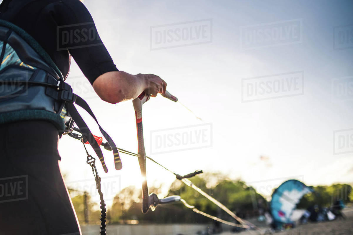 A woman in a wetsuit rigs up her kite on the beach before kiteboarding Royalty-free stock photo
