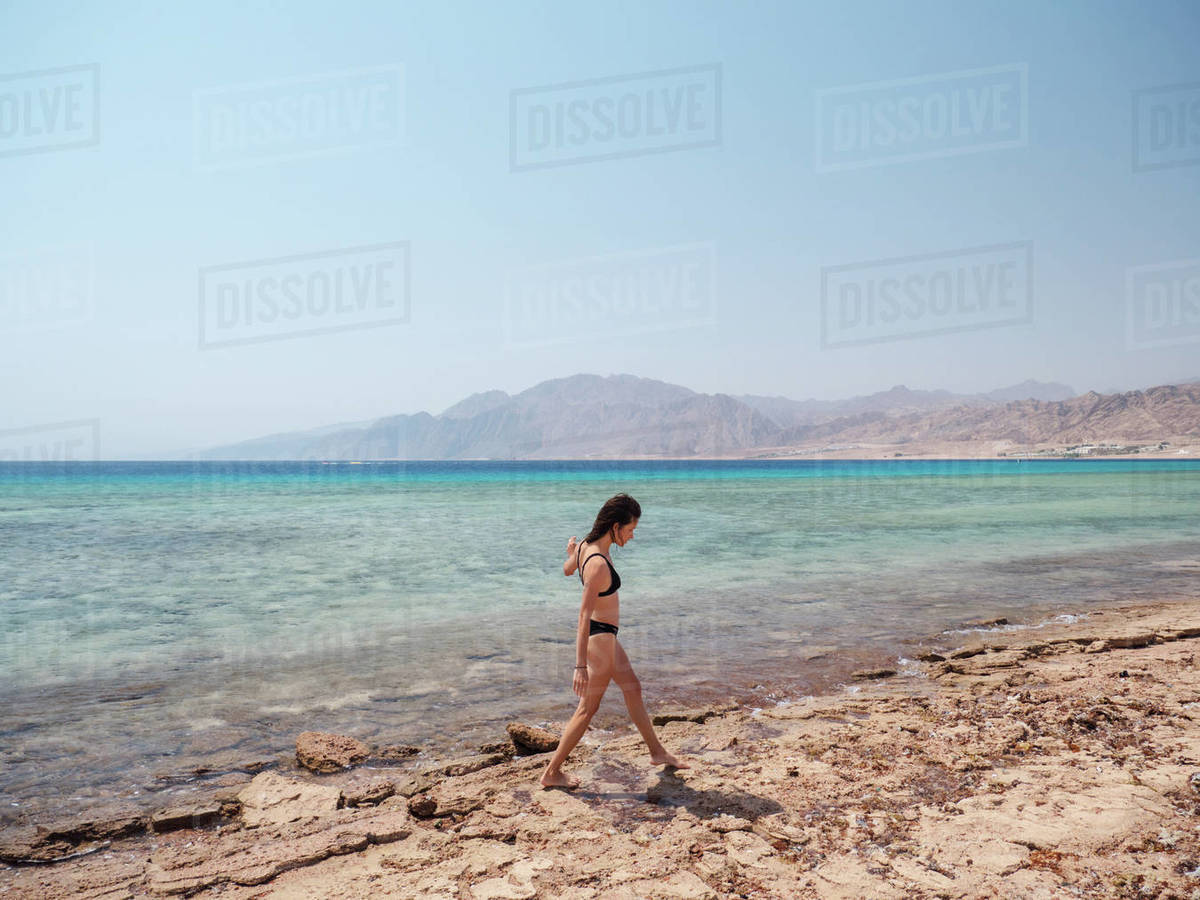 Young brunette woman relaxing on the beach near sea and mountains Royalty-free stock photo