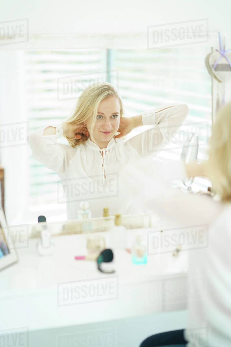 Jung woman looking in to the mirror and styling her hair Royalty-free stock photo
