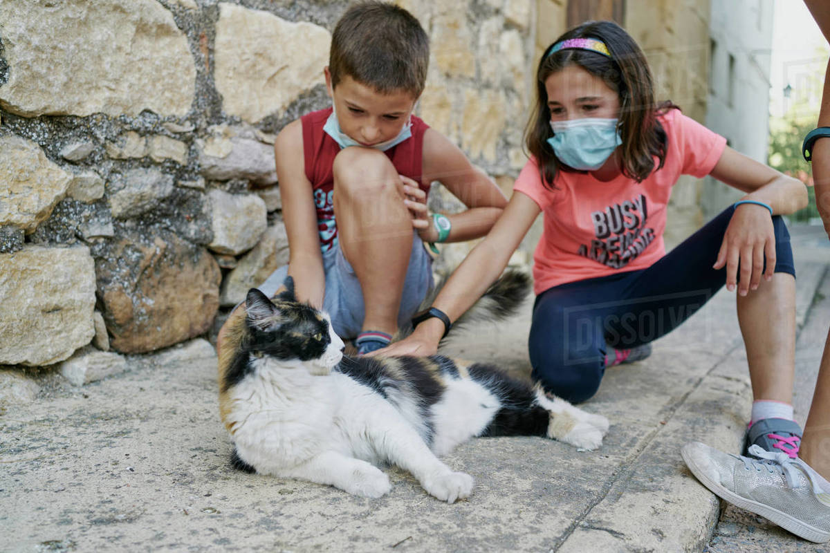 Two children with masks for the covid19 play with a black and white cat that is lying in the street Royalty-free stock photo