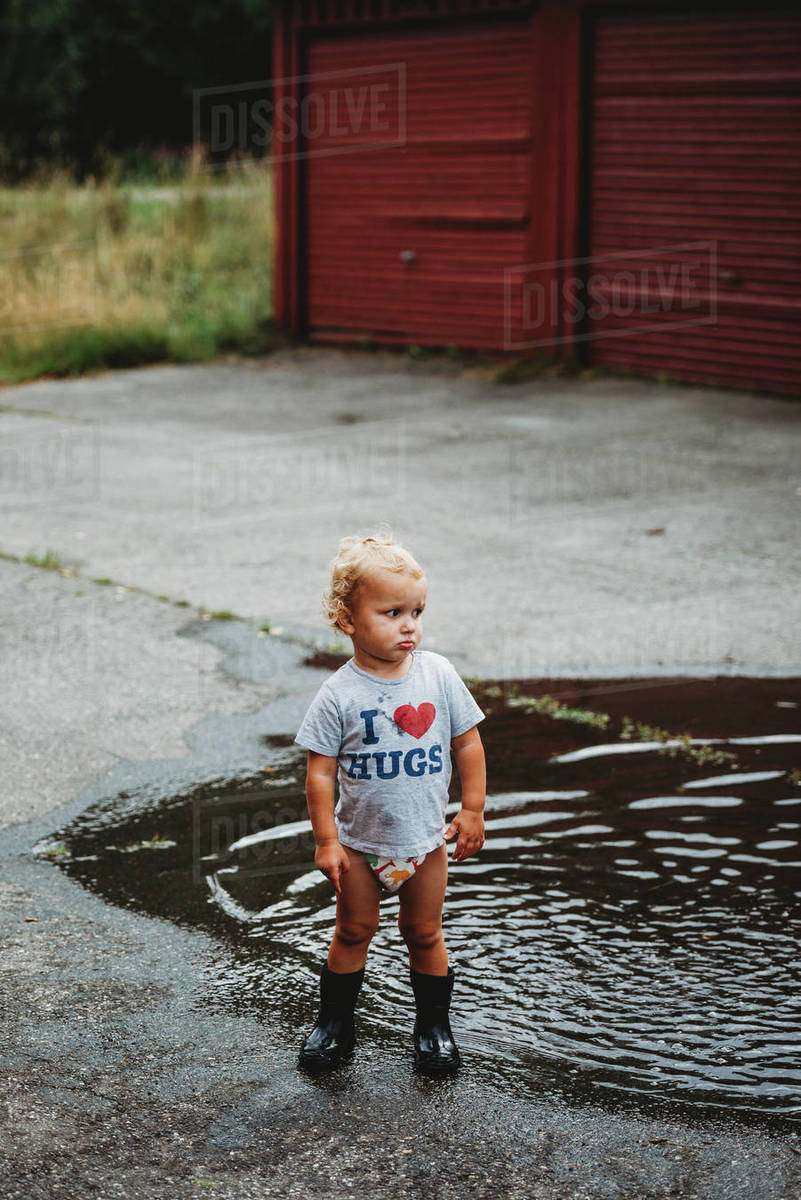 Adorable young boy pouting wearing rubber boots next to a puddle Royalty-free stock photo