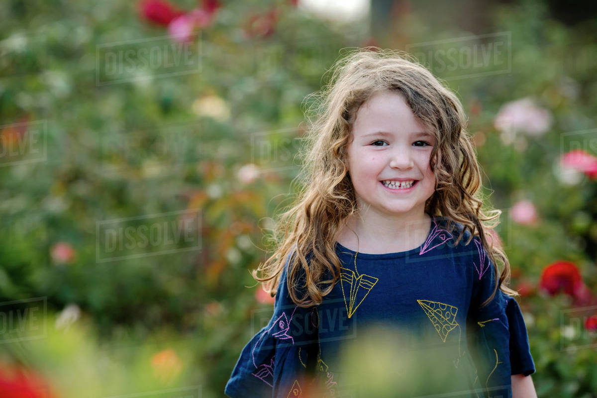 Smiling young girl with long wavy hair standing among flowers Royalty-free stock photo