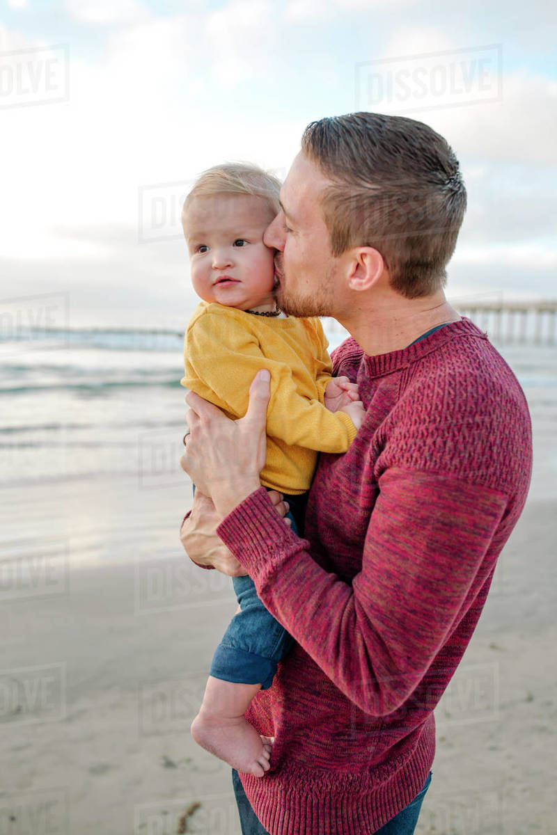 Loving dad kissing cheek of 6 month old baby at ocean near pier Royalty-free stock photo