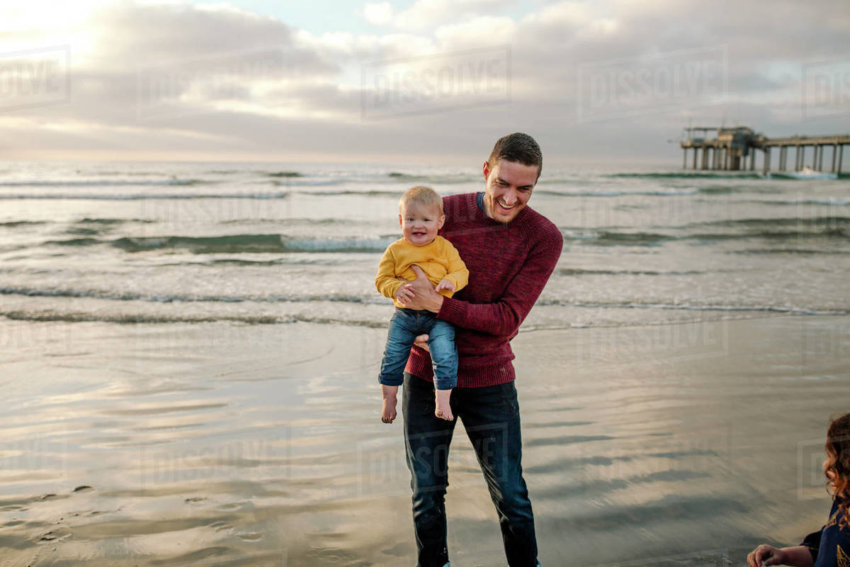 Laughing dad and 6 mo old baby wading in ocean near Scripps Pier Royalty-free stock photo