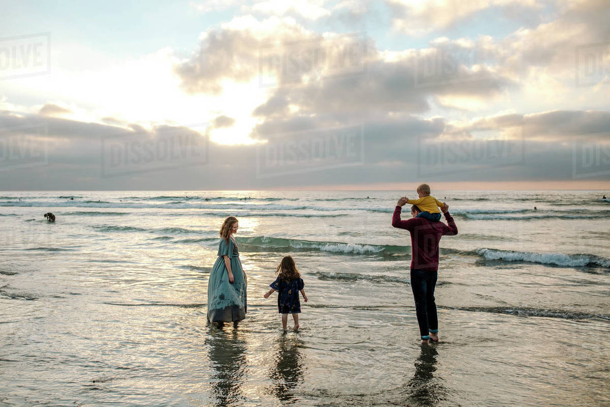 Family in street clothes playing in surf of ocean at sunset Royalty-free stock photo