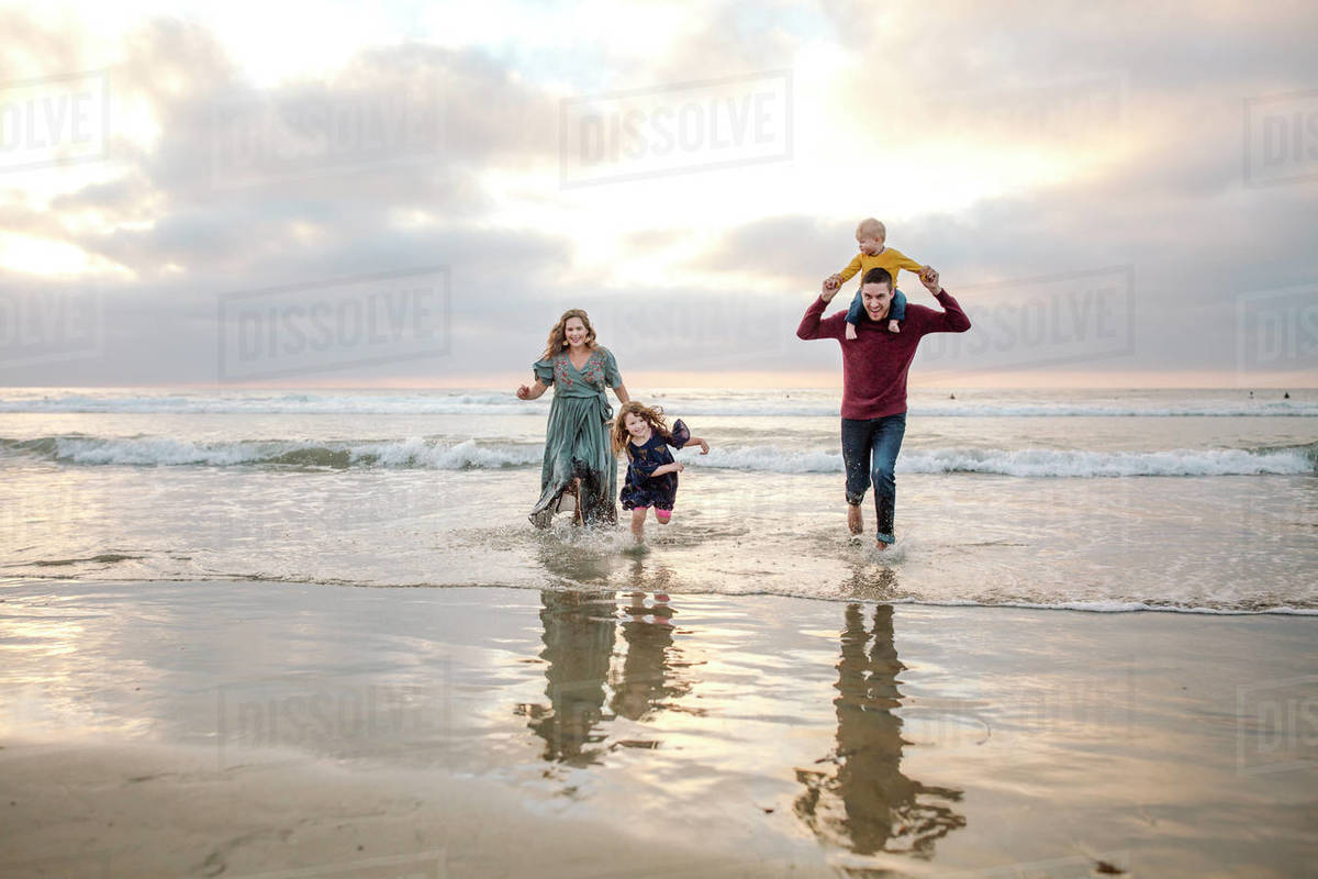 Adventurous young family running through ocean surf at sunset Royalty-free stock photo