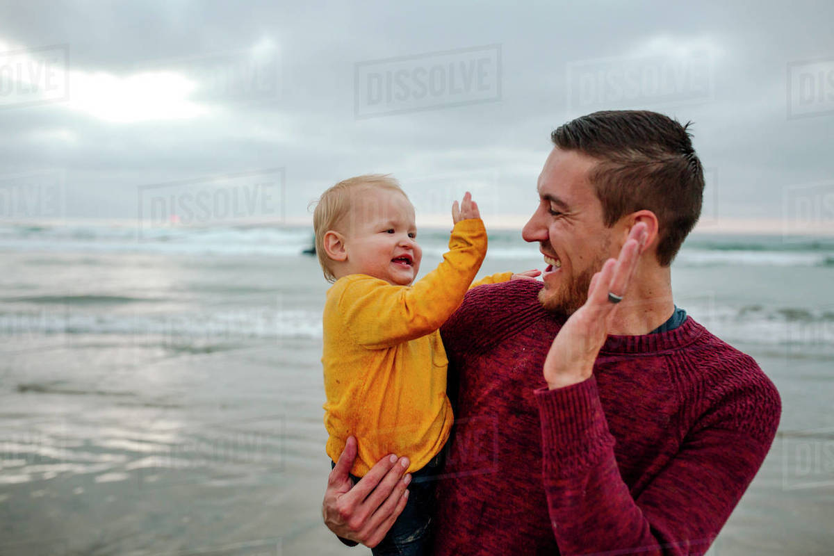 Laughing 30 yr old father holding baby at the ocean giving high-fives Royalty-free stock photo