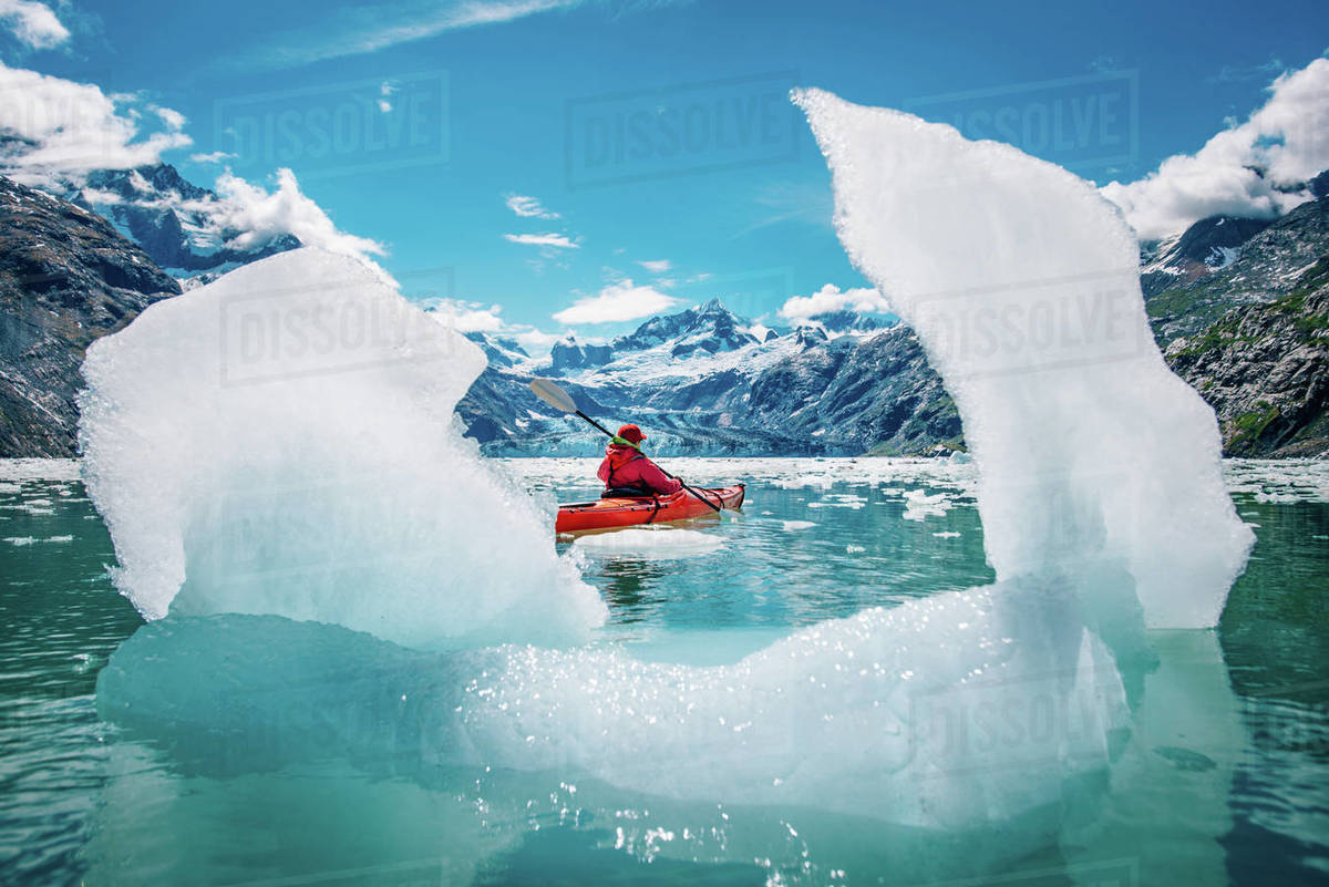 Woman kayaking in Glacier Bay National Park with iceberg in foreground Royalty-free stock photo