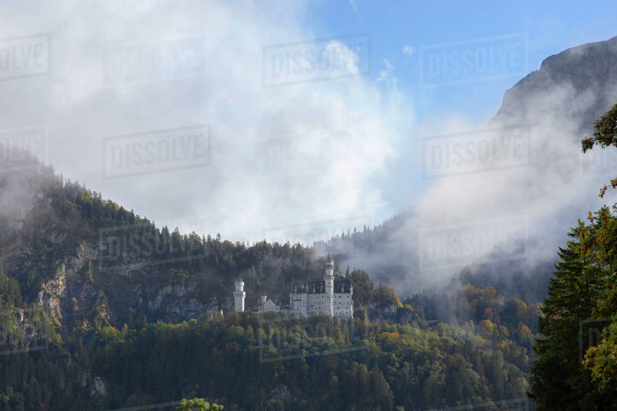 Castle Neuschwanstein through the mist on a mountainside in Germany Royalty-free stock photo