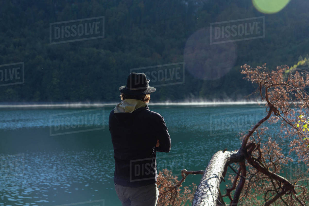 A hatted man looking across a clear alpine lake in Germany Royalty-free stock photo