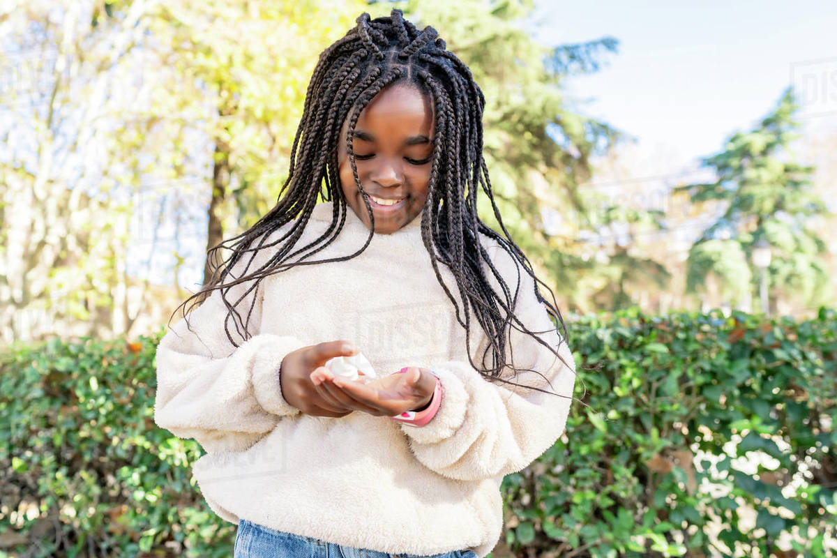 Beautiful african girl disinfecting her hands to avoid covid19 Royalty-free stock photo