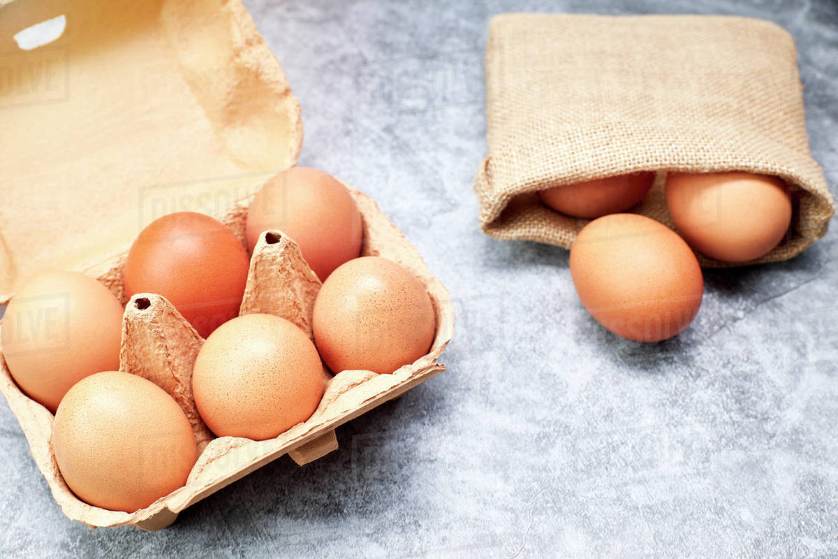 Chicken eggs in their carton and raffia bag. Healthy food concept Royalty-free stock photo