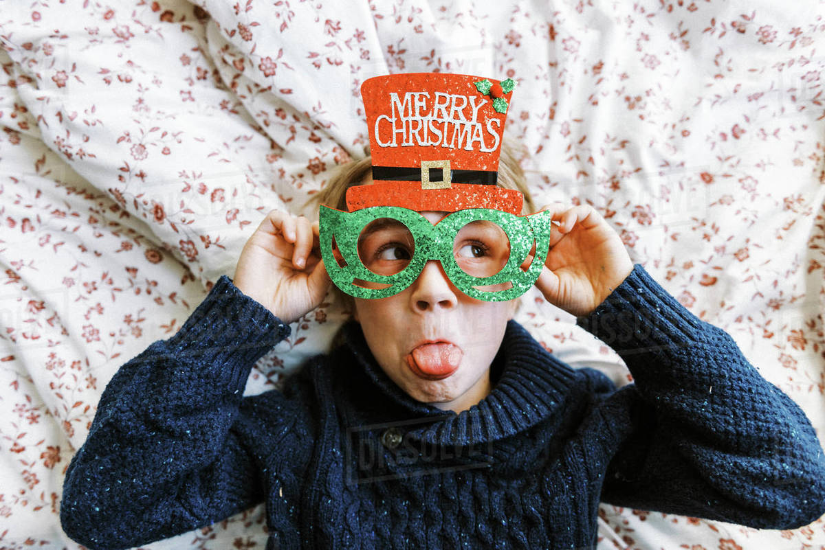 Little boy in a knit sweater with Christmas glasses lying on bed Royalty-free stock photo