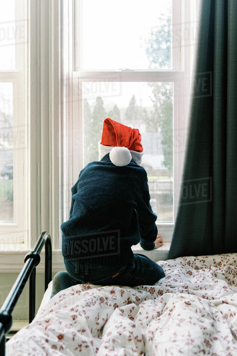 Little boy with Christmas hat looking out the window for Santa clause Royalty-free stock photo
