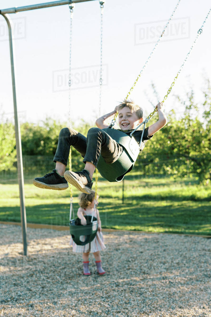 Little boy swinging high on a baby swing and having fun Royalty-free stock photo