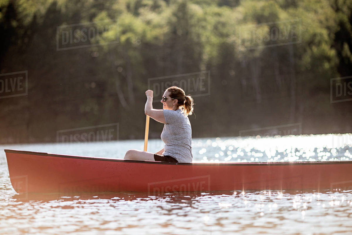 Woman paddles red canoe across lake in sunshine in Maine woods Royalty-free stock photo