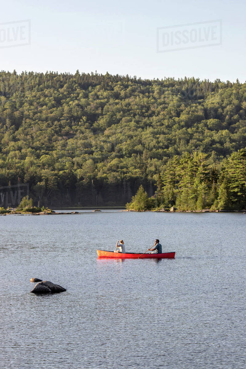 Man and woman paddle boat canoe on beautiful pond lake in Maine Royalty-free stock photo