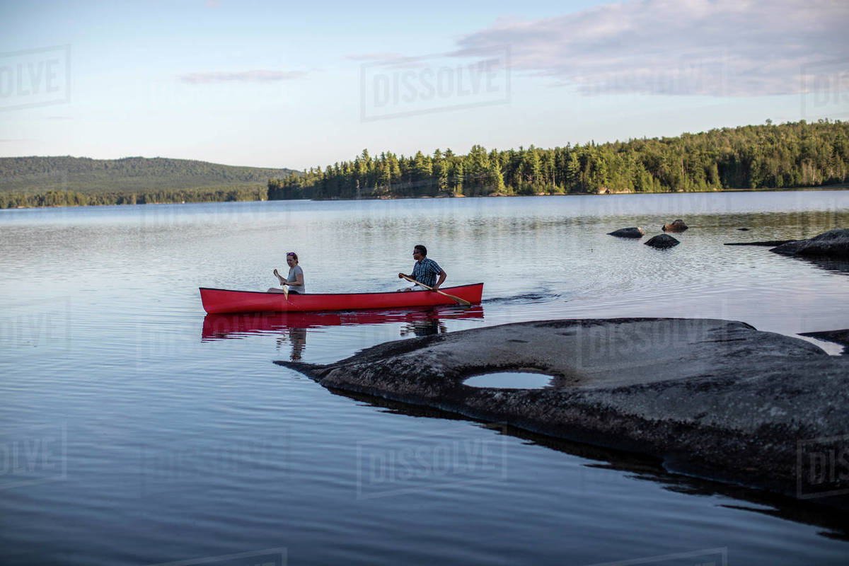 Paddlers steer canoe past rocky point in wilderness lake in Maine Royalty-free stock photo