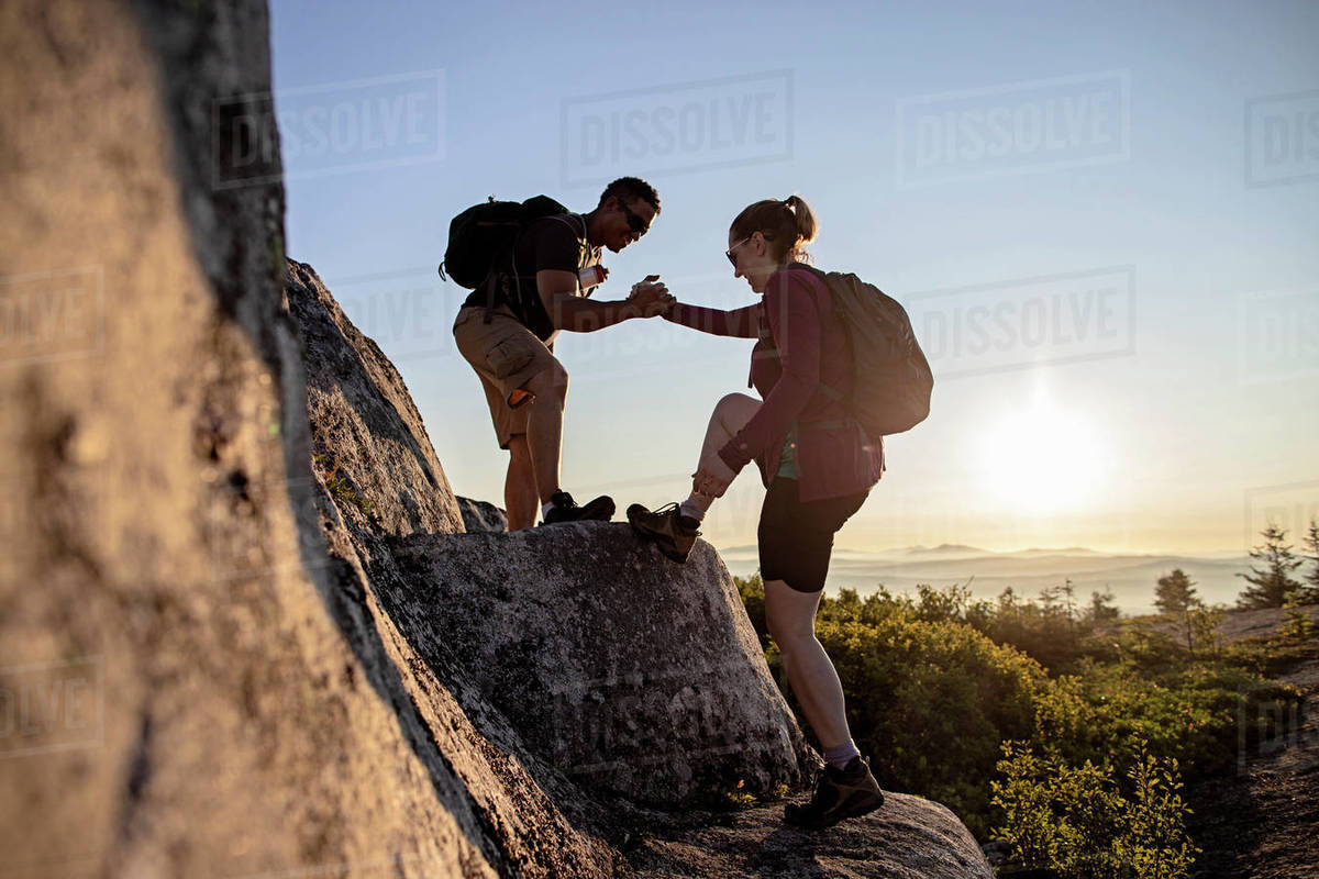 Two hikers help each other up mountain on Appalachian Trail in Maine Royalty-free stock photo