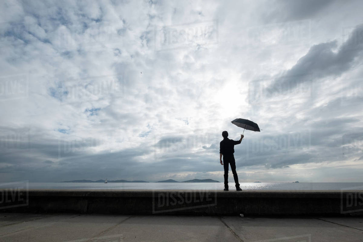 Young boy holding an umbrella by the sea Royalty-free stock photo