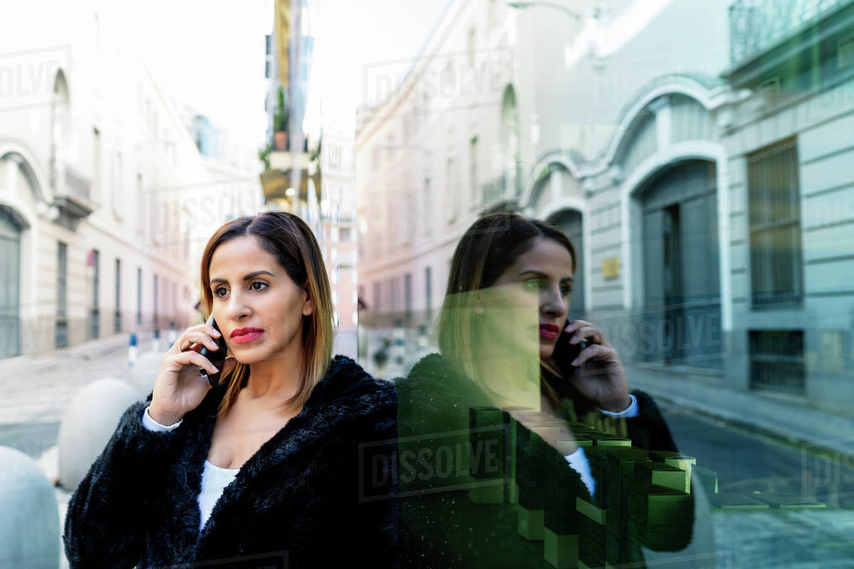 Executive woman in black jacket talking on her smartphone Royalty-free stock photo
