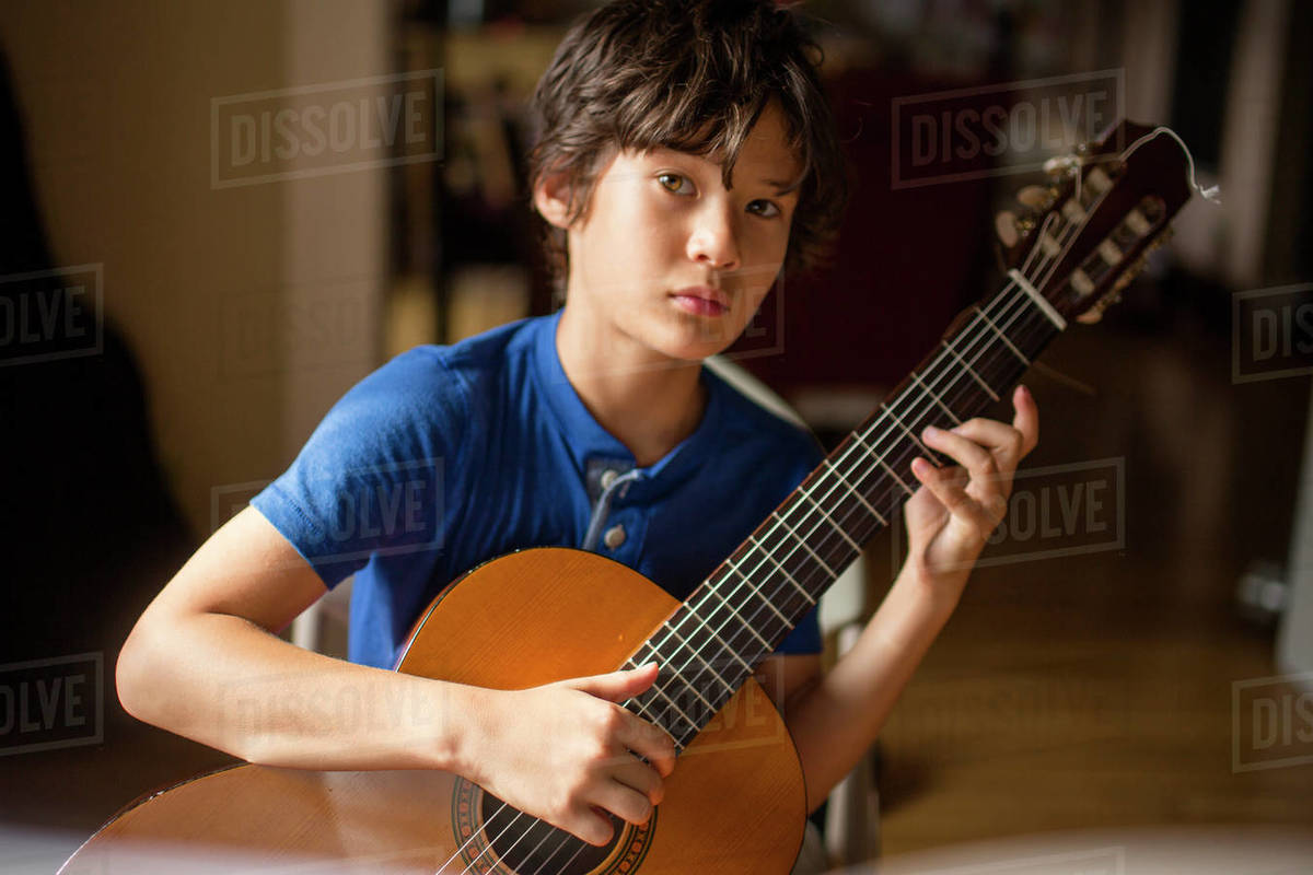 A boy with direct gaze and serious expression holds a classical guitar Royalty-free stock photo