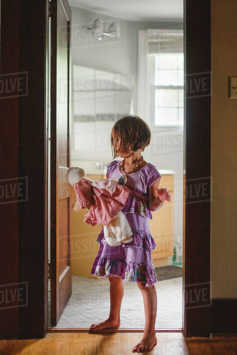 A barefoot child stands alone in doorway holding a stuffed animal Royalty-free stock photo