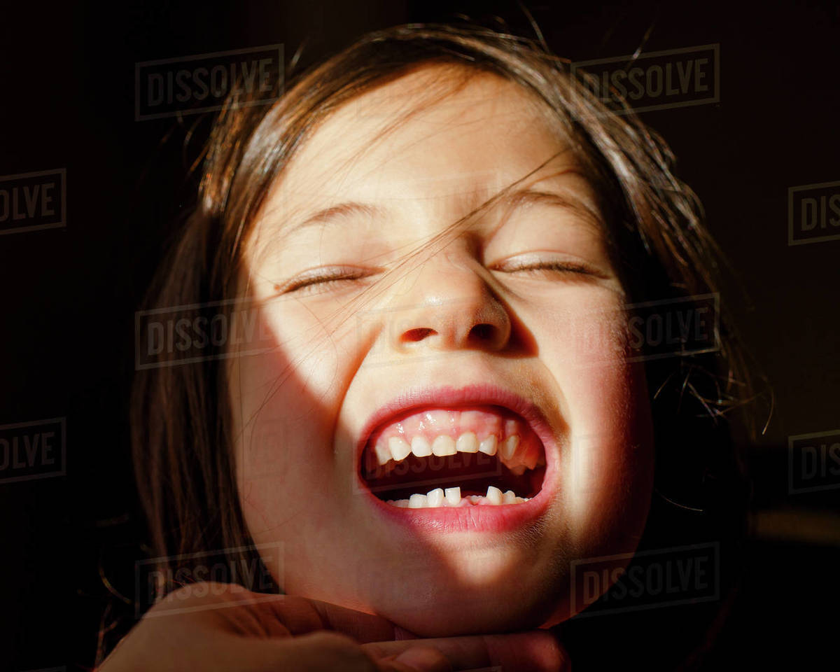 A small girl with eyes closed tilting up head to show first lost tooth Royalty-free stock photo
