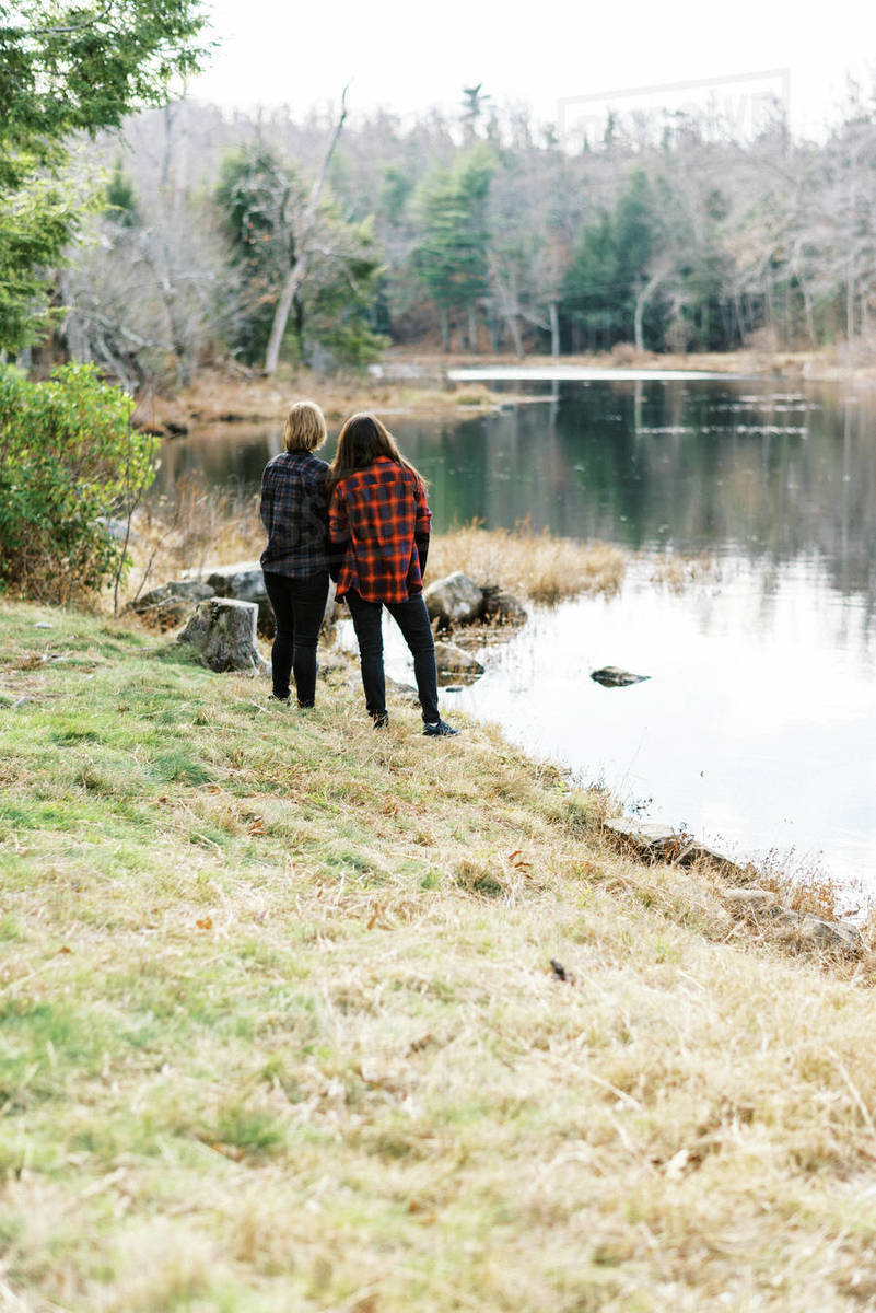 A couple standing by the shore of a river together holding hands Royalty-free stock photo