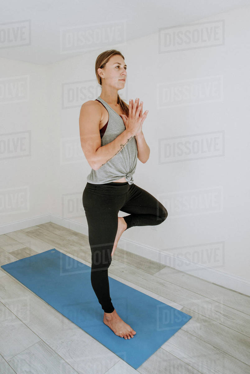 Woman concentrates while doing simple yoga pose indoors on blue mat Royalty-free stock photo