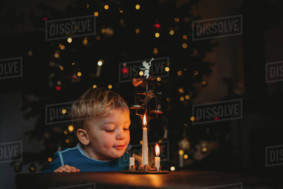Adorable young child blowing candles with lit up Christmas tree behind Royalty-free stock photo