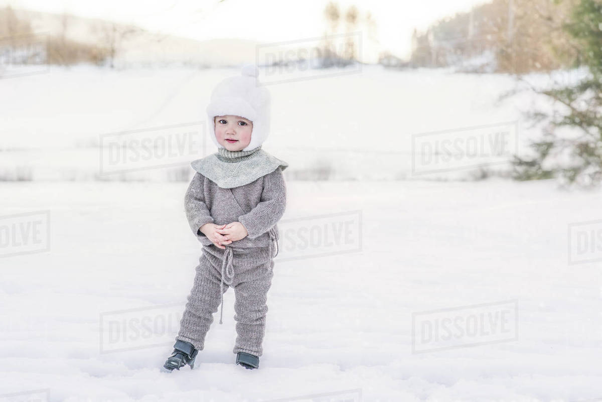 Adorable child standing in snow at farm wearing wool knitted clothes Royalty-free stock photo