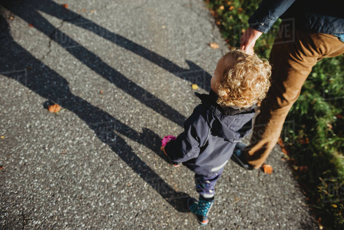 Father and son holding hands walking in the street Royalty-free stock photo